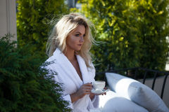 Beautiful young woman in Bathrobe sitting on terrace and drink coffee. Beautiful young woman in Bathrobe sitting on the terrace and drink coffee stock image