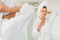 Beautiful young woman in bathrobe and towel on head looking at mirror. In bathroom royalty free stock photography