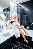Beautiful young woman in bathrobe and towel on her head sitting on a bathtub. And pours tea royalty free stock photography