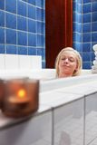 Beautiful young woman in bathtub with eyes closed. Beautiful young woman in bathtub at luxury spa with candle in glass Royalty Free Stock Photos