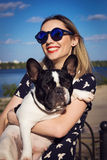 Beautiful young woman on the beach with french bulldog Stock Images