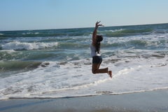 Beautiful young woman on the beach jumping for joy. Above oncoming ocean waves Royalty Free Stock Images