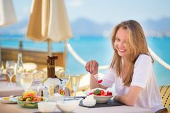 Beautiful young woman in a beach restaurant. Beautiful young woman eating fruits in a beach restaurant stock photos