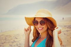 Beautiful young woman on the beach with sunglasses and straw hat smiling at camera. Traveler girl in her summer holidays in Canary Stock Images