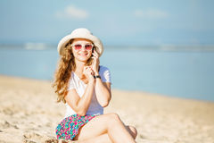 Beautiful young woman at the beach talking on Royalty Free Stock Images