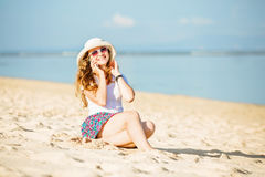 Beautiful young woman at the beach talking on Stock Photos