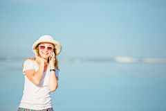 Beautiful young woman at the beach talking on Stock Image