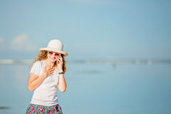 Beautiful young woman at the beach talking on Royalty Free Stock Photography