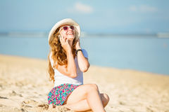 Beautiful young woman at the beach talking on Stock Photography