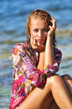 The beautiful young woman on a beach in a wet dres Stock Images