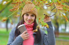 Beautiful young woman with beanie hat in park in autumn holding takeaway coffee cup Royalty Free Stock Photos