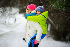 Beautiful young woman bears on the son`s shoulders through snowdrifts. Royalty Free Stock Images