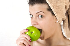 Beautiful young woman beating an apple. Royalty Free Stock Image