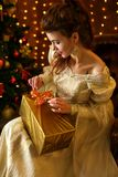 Beautiful young woman in a beautiful dress sitting at the Christmas tree with gifts, Christmas and new year stock photos