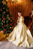 Beautiful young woman in a beautiful dress sitting at the Christmas tree with gifts, Christmas and new year royalty free stock photography