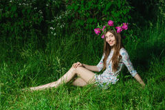 Beautiful young woman with beautiful legs in green spring grass Royalty Free Stock Photo