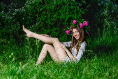 Beautiful young woman with beautiful legs in green spring grass Stock Images