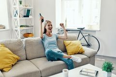Beautiful young woman. Cheering and smiling while watching TV on the sofa at home royalty free stock photos