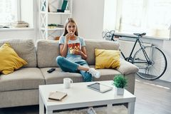 Beautiful young woman. Eating popcorn while watching TV on the sofa at home stock photos