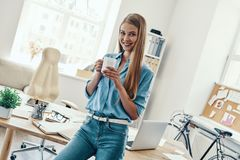 Beautiful young woman. In smart casual wear looking at camera and smiling while standing in the office stock image