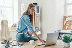 Beautiful young woman. In smart casual wear using laptop while working in the office royalty free stock photography