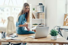 Beautiful young woman. In smart casual wear using laptop while working in the office royalty free stock photo