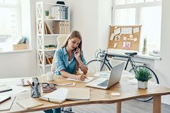 Beautiful young woman. In smart casual wear writing something down and talking on the phone while sitting in the office royalty free stock images