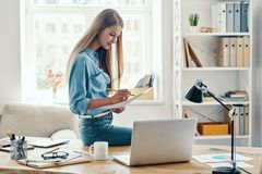 Beautiful young woman. In smart casual wear writing something down and using laptop while sitting in the office royalty free stock photo