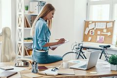 Beautiful young woman. In smart casual wear writing something down and using laptop while sitting in the office stock photo