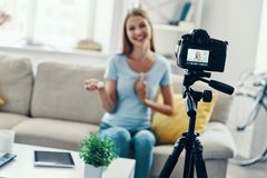Beautiful young woman. Smiling and gesturing while making social media video at home royalty free stock photo
