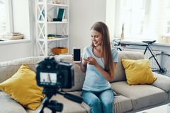 Beautiful young woman. Smiling and pointing copy space on her smart phone while making social media video at home stock image