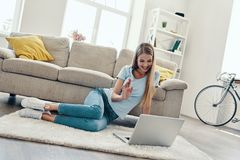 Beautiful young woman. Waving with smile and using laptop while resting at home stock images