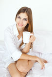 Beautiful  young woman in bed with cup of coffee Stock Photos