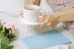 Beautiful young woman in bed drinking tea reading book stock photography