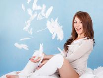 Beautiful young woman in a bed dropping the feathers Royalty Free Stock Photo