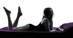 Beautiful young woman in bed full length silhouette Stock Images