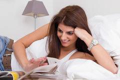 Beautiful young woman on the bed reading magazine Stock Photos