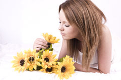 Beautiful young woman in bed with sunflowers Stock Images