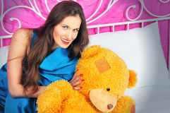 Beautiful young woman on a bed with teddy bear Royalty Free Stock Image