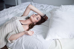 Beautiful young woman in bedroom Stock Images