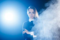 Beautiful young woman behind the cloud of smoke Stock Photos