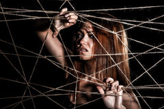 Beautiful young woman behind the interlaced ropes Stock Image