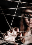 Beautiful young woman behind the interlaced ropes Royalty Free Stock Images