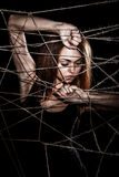 Beautiful young woman behind the interlaced ropes Stock Photos