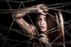 Beautiful young woman behind the interlaced ropes Stock Images