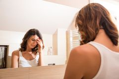 A beautiful young woman in the bathroom. A beautiful young woman being sad at the mirror in the bathroom royalty free stock image