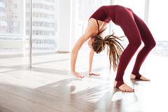 Beautiful young woman  bending and doing yoga in studio Royalty Free Stock Photography