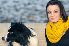 Beautiful young woman with best dog friend in winter. Young adult and her best friend sitting on a bench in winter. The dog is a border collie. With copy space Royalty Free Stock Images