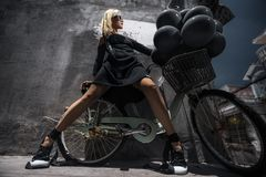 Woman with black baloons. Beautiful young woman with bicycle posing on the street with a lot of black baloons royalty free stock photo