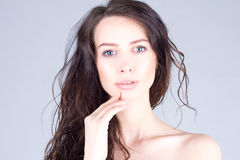 Beautiful young woman with big blue eyes and curly hair touching lips. Beautiful face of woman. Stock Images
